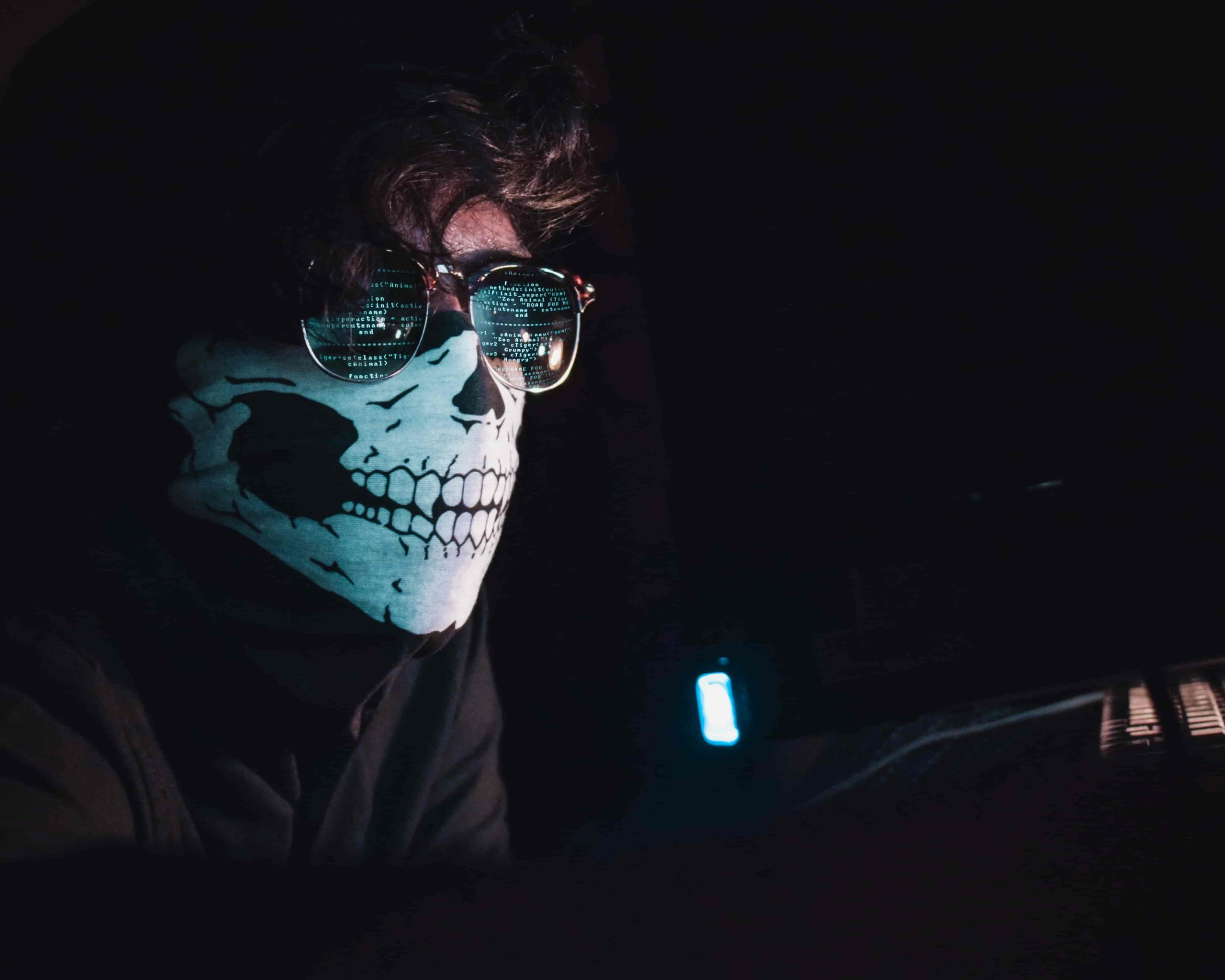 Cyber Hacker with skeleton mask and computer reflected in glasses